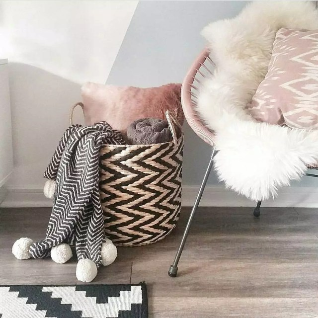 Cute storage basket with blankets and throw pillows next to chair. Photo by Instagram user @caffeineandcacti
