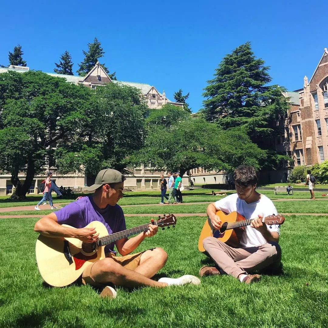 College Students Seated on the Ground Playing Guitar. Photo by Instragram user @uofwa