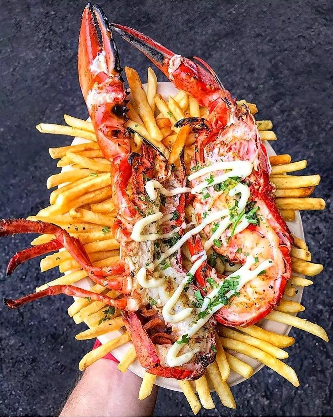 Large plate of fries topped with lobster tails Photo by Instagram user @smorgasburg