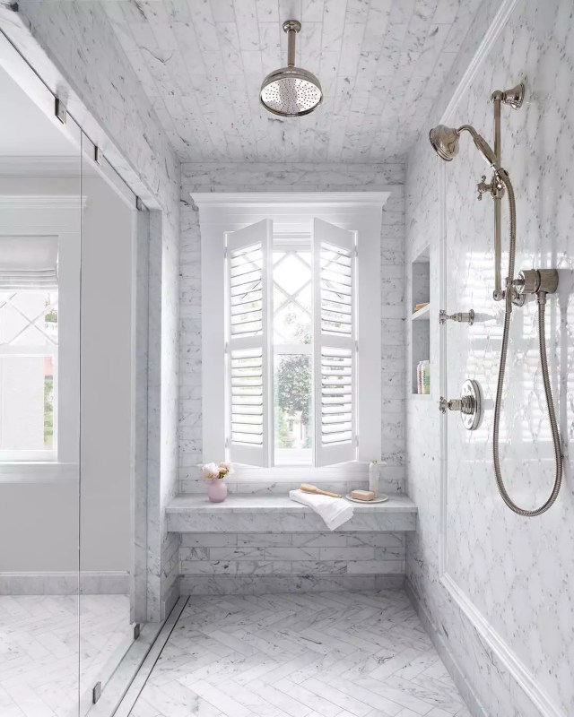 gray tile in large shower with shower bench and window photo by Instagram user @oakhillarchitects