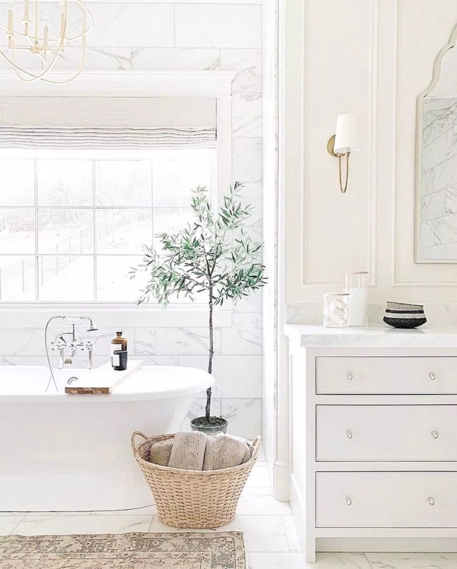 bathroom with lots of natural light next to soaking tub with small shrub in the bathroom photo by Instagram user @chandeliers.and.champagne