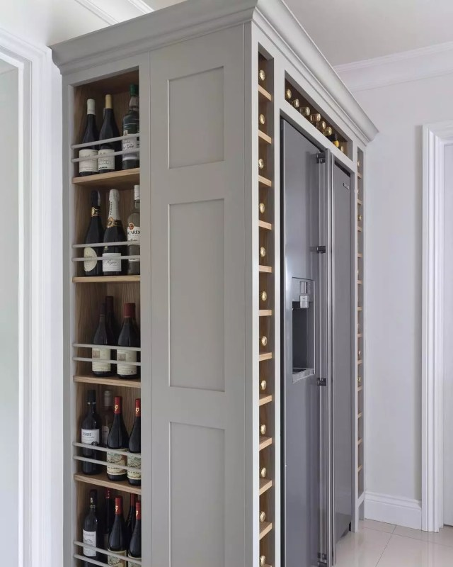 Custom-built wine storage around refrigerator. Photo by Instagram user @charliekinghamcabinetmakers