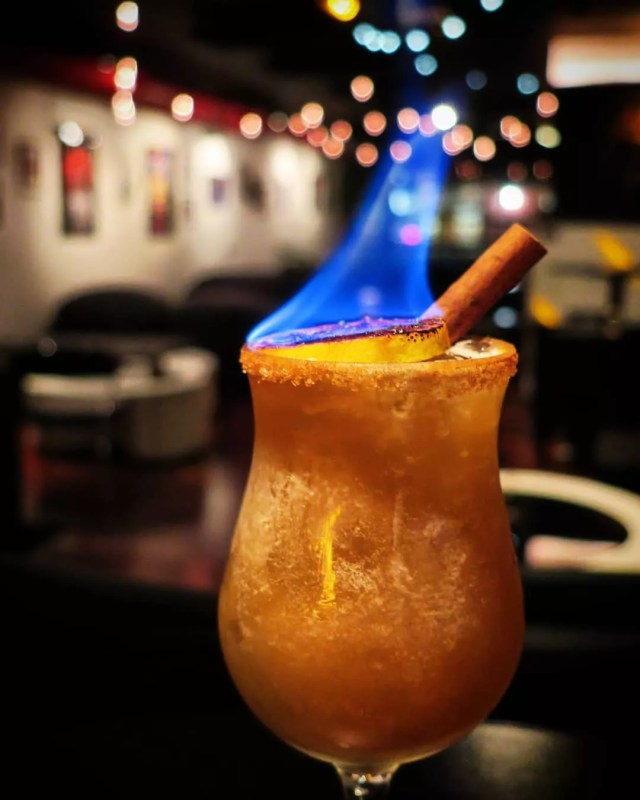 Rum drink in a hurricane glass with a cinnamon stick and piece of lemon on fire. Photo by Instagram user @mixtapepgh