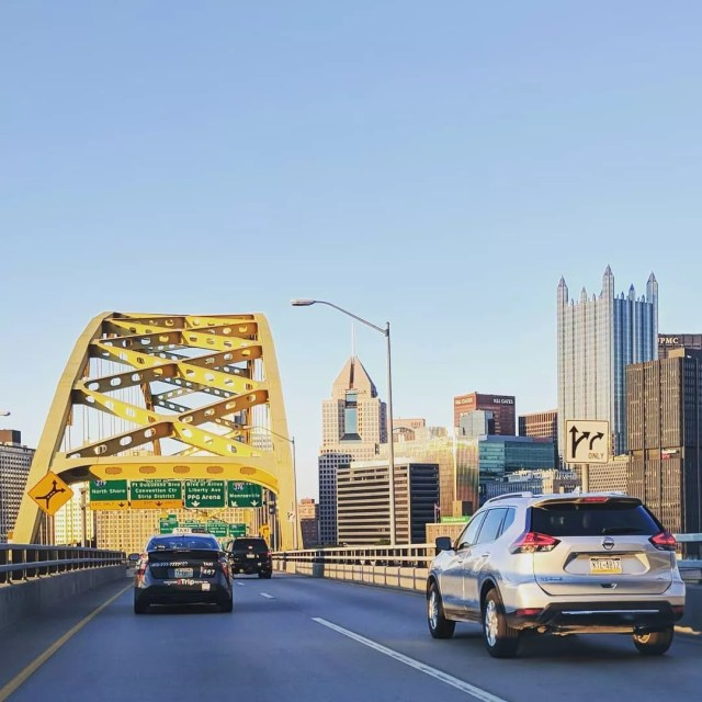 Cars drive across bridge in Pittsburgh with skyline on the right side. Photo by Instagram user @theaaronm