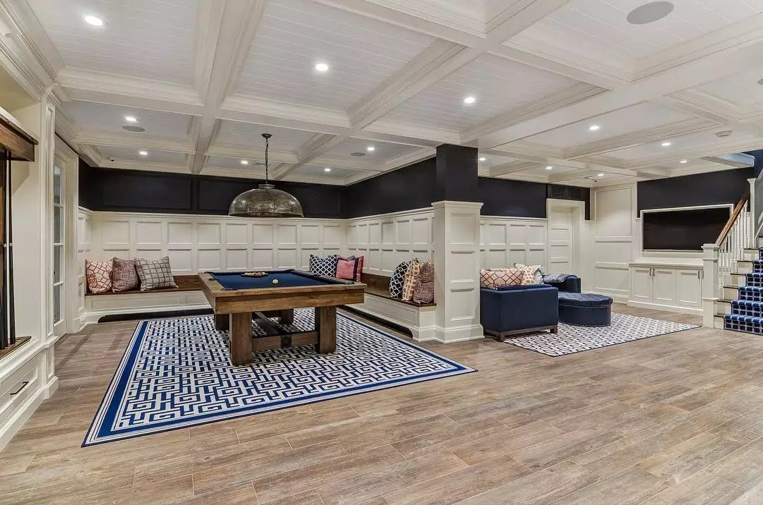 Large Finished Basement with Wood Floors and Area Rugs. Photo by Instagram user @mcad_design