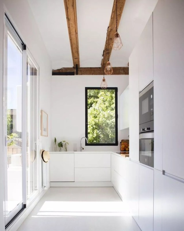 Modern minimalist kitchen with no hardware on doors. Photo by Instagram user @jutrufelliarq