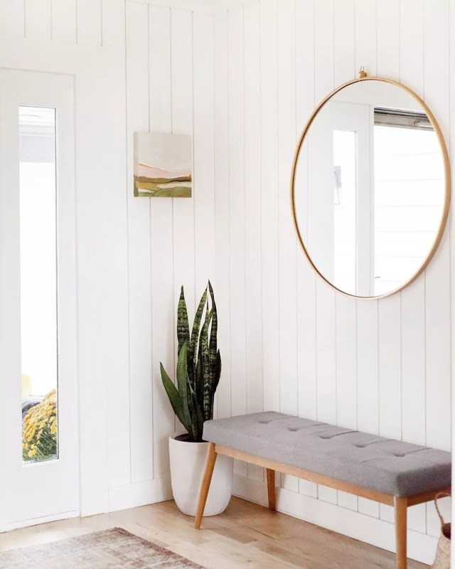 Entryway with shiplap walls and minimalist decor. Photo by Instagram user @kellikroneberger