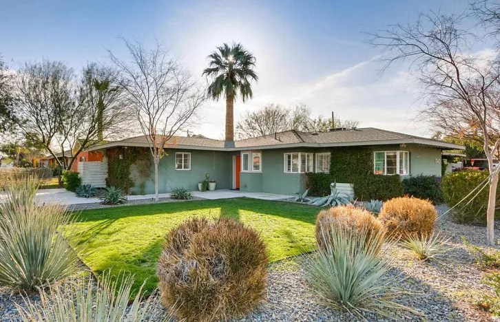 Side view of ranch-style single-family home with teal paint, green grass in the foreground and a palm tree in the background Photo by Instagram userazhomeforsale