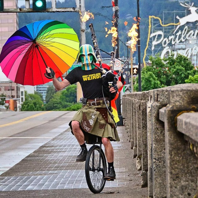 Man on a unicycle wearing a kilt, holding a colorful umbrella and a flaming bagpipe wearing a colorful Darth Vadar mask Photo by Instagram @theunipiper