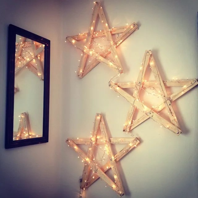 Homemade Wooden Stars Wrapped in Christmas Lights Hanging on Wall in Home. Photo by Instagram user @joelsp84