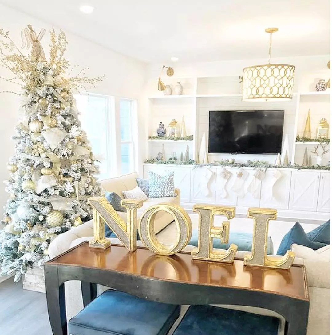 Couches and Christmas Tree in Living Room with NOEL Letters on Table. Photo by Instagram user @caliber_homes