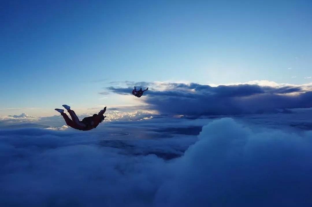 Couple Skydiving Above the Clouds. Photo by Instagram user @floorgaasbeek