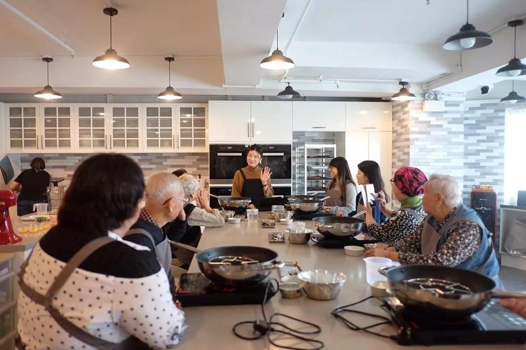 Group of Elderly Men & Women Taking a Cooking Class. Photo by Instagram user @cookingemem