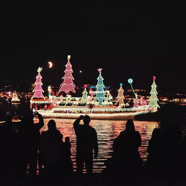 Boat lit up with Christmas lights in the water. Photo by Instagram user @visitnewportbeach