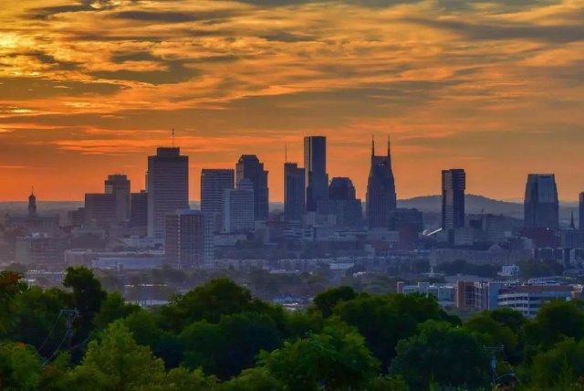 View of Nashville skyline at sunset with orange sky. Photo by Instagram user @newschannel5