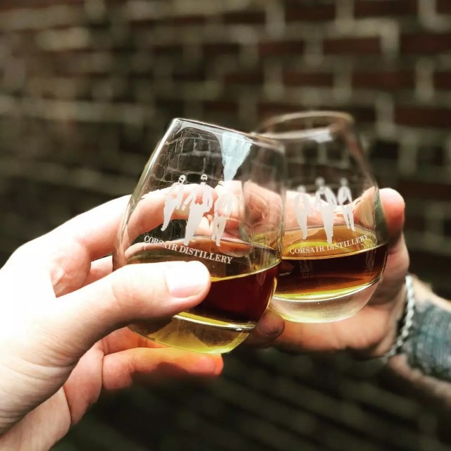 Two people clinking glasses with whiskey. Photo by Instagram user @corsairdistillery