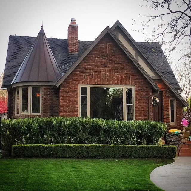Front of single-family brick home with a spire and large picture window in front. Photo by Instagram user @lovelyoldhomes