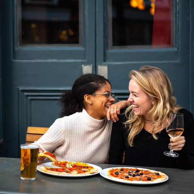 Two Women Eating Pizza on a Patio During a Date. Photo by Instagram user @thebelrose_pub