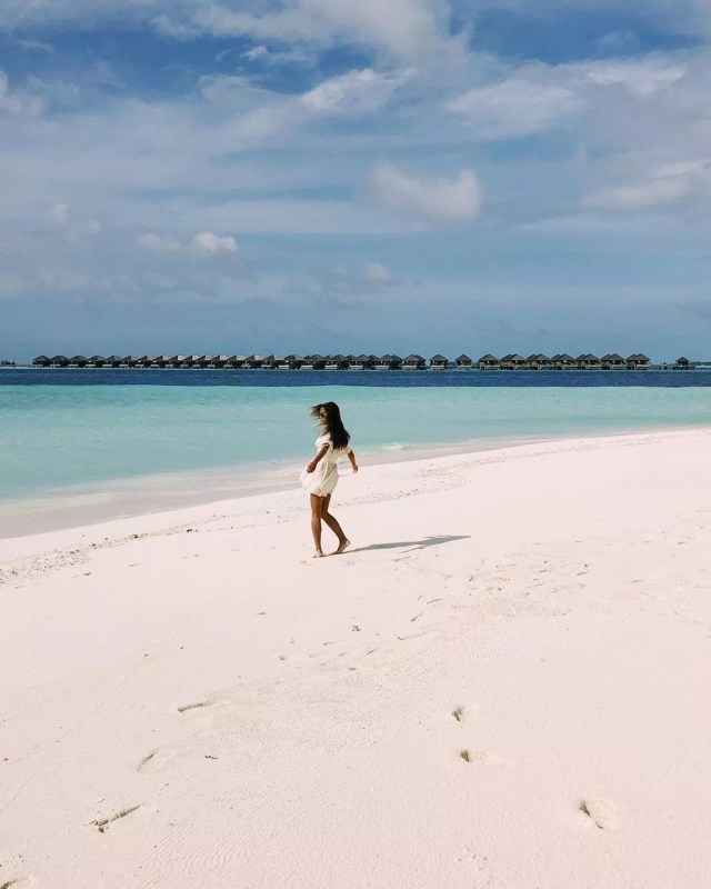 Woman Walking on a White Sand Beach. Photo by Instagram user @misselectrify
