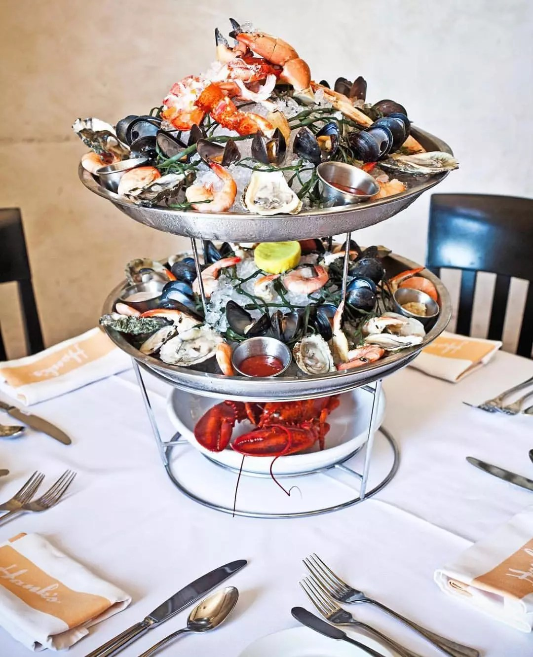 Multiple types of seafood piles on a multi-tiered serving tray. Photo by Instagram user @hanksseafood
