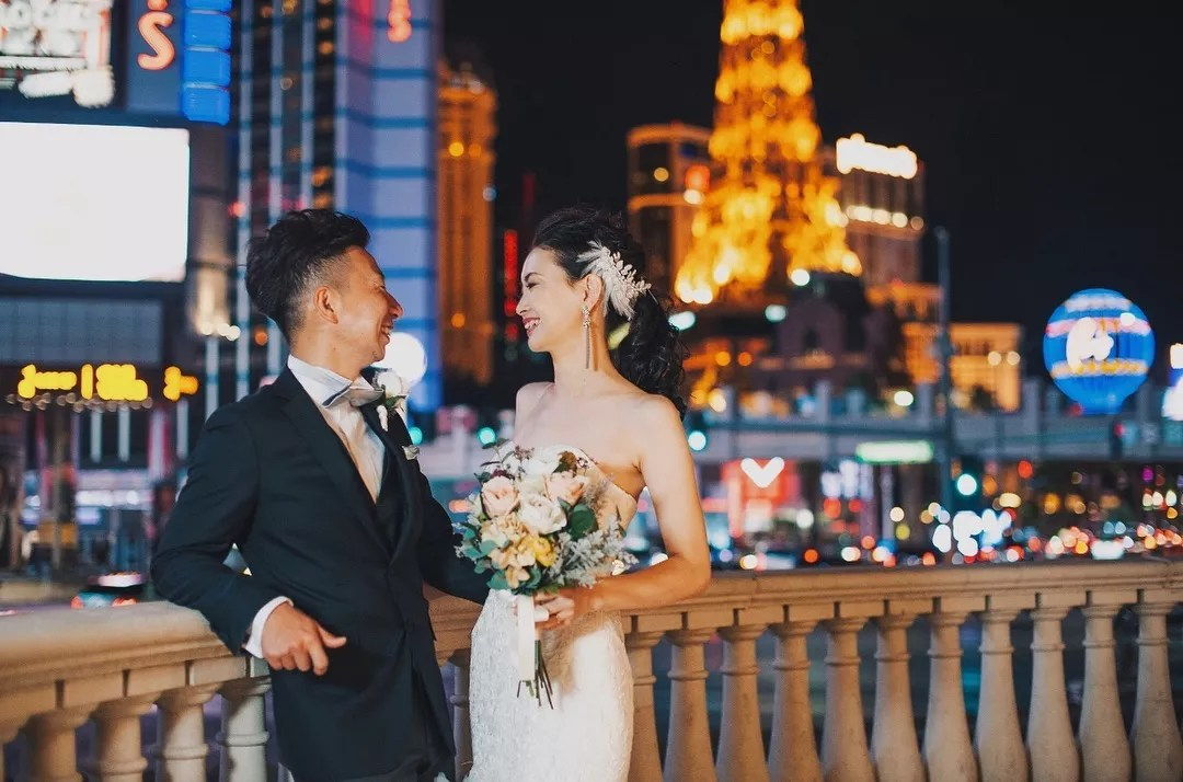 Bride and Groom Smiling at Each Other on the Las Vegas Strip. Photo by Instagram user @hazukiphotography