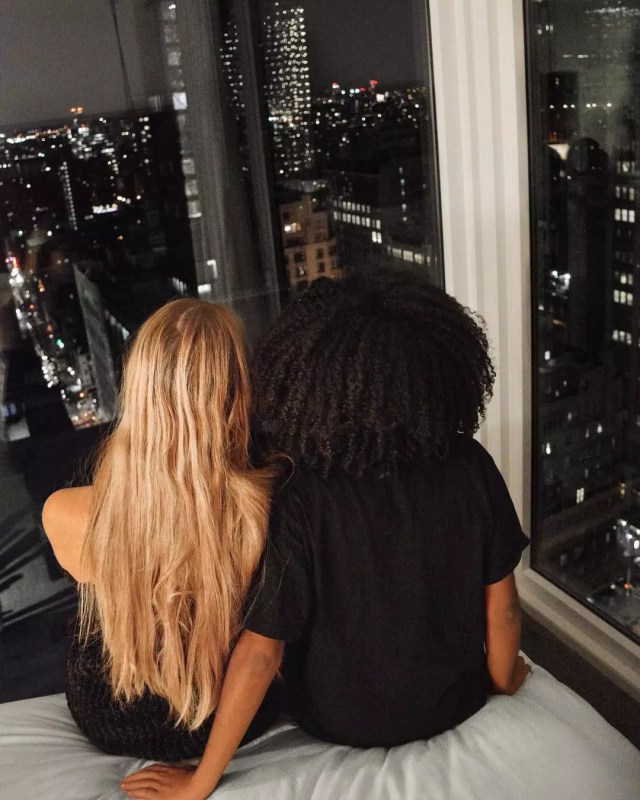 Couple Overlooking a City at Night from a Hotel Room. Photo by Instagram user @theangelinos_