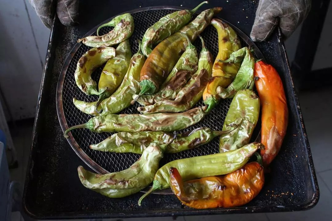 Large hatch chiles roasting on a grill. Photo by Instagram user @visitabq