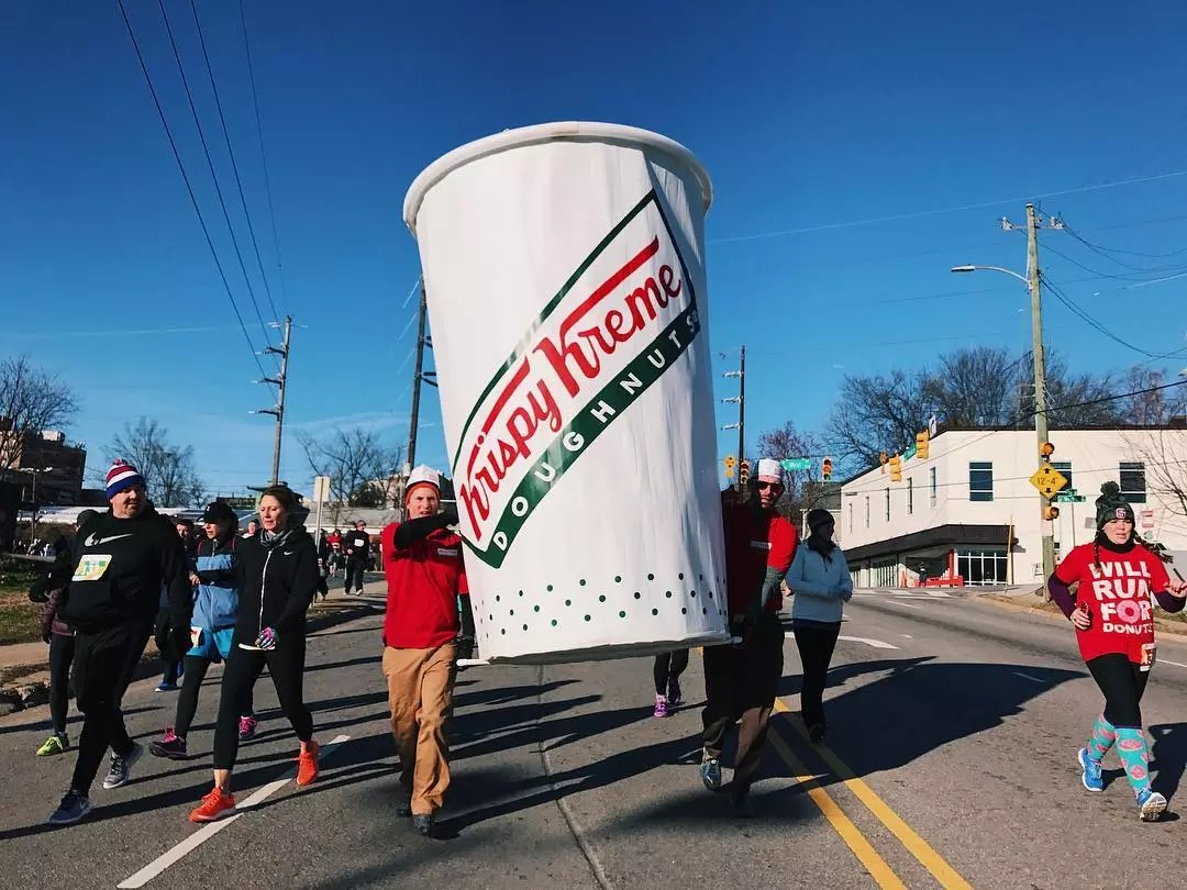 Runners holding a large Krispy Kreme Doughnuts coffee cup during a race. Photo by Instagram user @ncstate