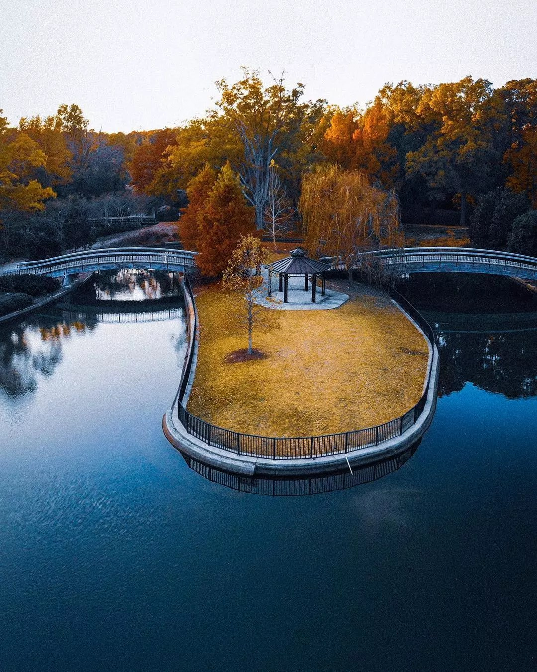 Overhead view of pond and greenspace with bridges and shelter at Pullen. Park Photo by Instagram user @rawsta_photo