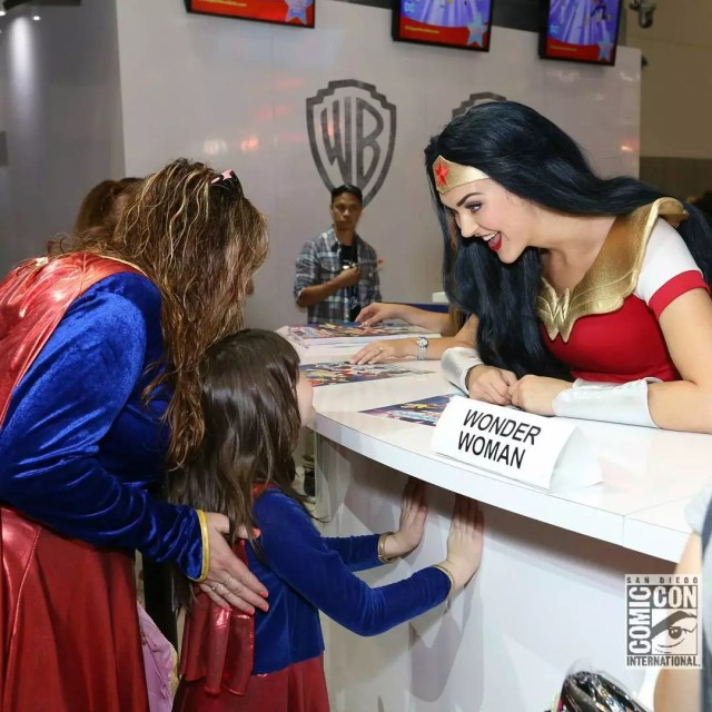 A woman dressed up as wonder woman greets a young child and older woman both dressed as super woman. Photo by Instagram user @comic_con