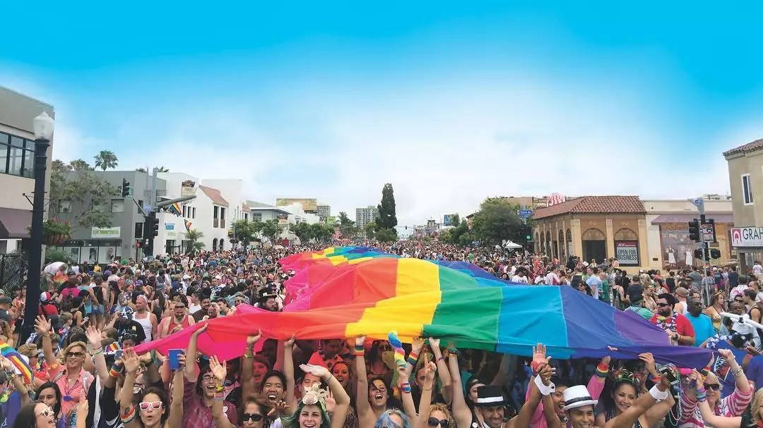 A large group of people stand on the street holding a giant rainbow flag above their head. Photo by Instagram user @sandiegopride