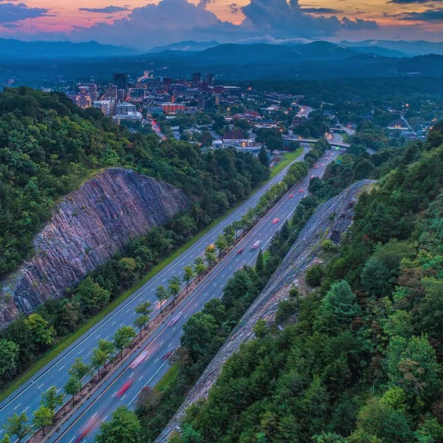 Aerial view of streets between cliffs of trees. Photo by Instagram user @overasheville