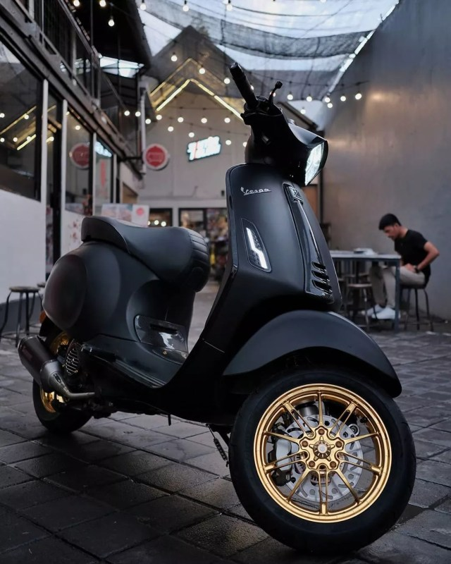 matte black motor scooter with gold rims photo by Instagram user @skuterkoloni