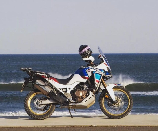 off-road bike with helmet resting on it in front of ocean photo by Instagram user @aoserow