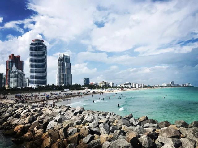 Tall buildings next to the ocean in Miami. Photo by Instagram user @jimmypolitan