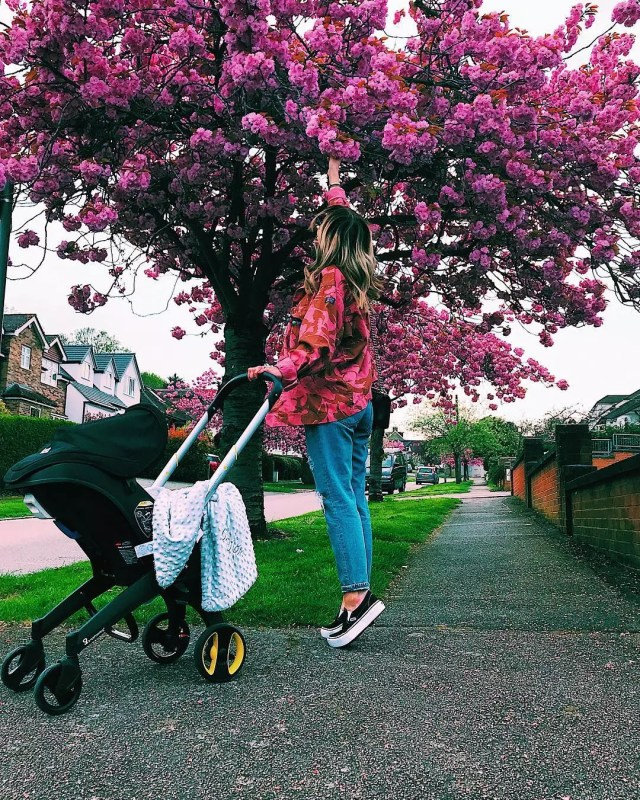 Woman picking pink flowers from a tree. Photo by Instagram user @astonmerrygold