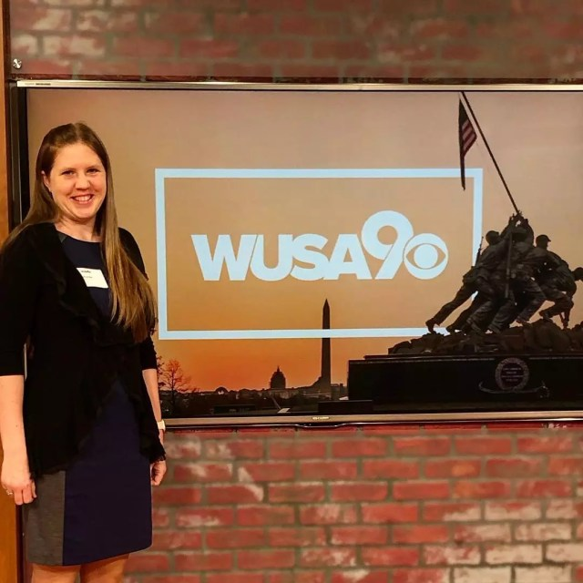Woman standing next to a news station sign at WUSA 9. Photo by Instagram user @airmantomom