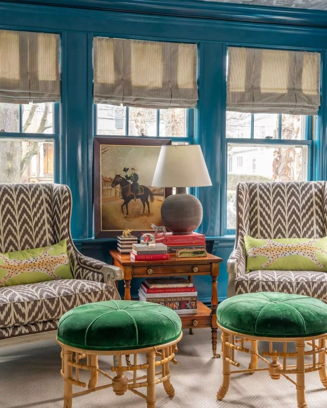 Living room with blue walls and patterned chairs with green stools in Ecelectic design. Photo by Instagram user @lizcaan
