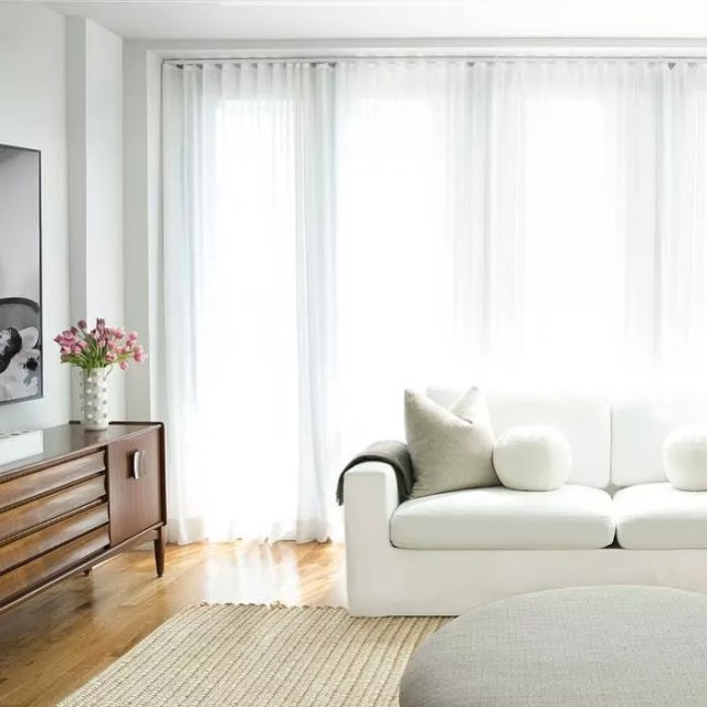 Living room with white curtain and a white comfy couch. Photo by Instagram user @carawoodhouseinteriors