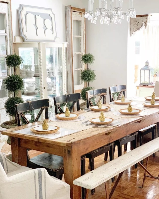 Long wood dining table with plates and gold pineapple statues on them. Photo by Instagram user @robyns_frenchnest