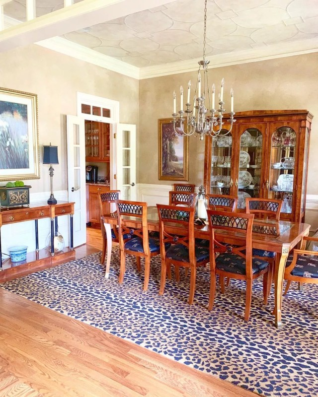 Dining room designed in Traditional style with an animal print rug and wood table with chandelier. Photo by Instagram user @betweenporches