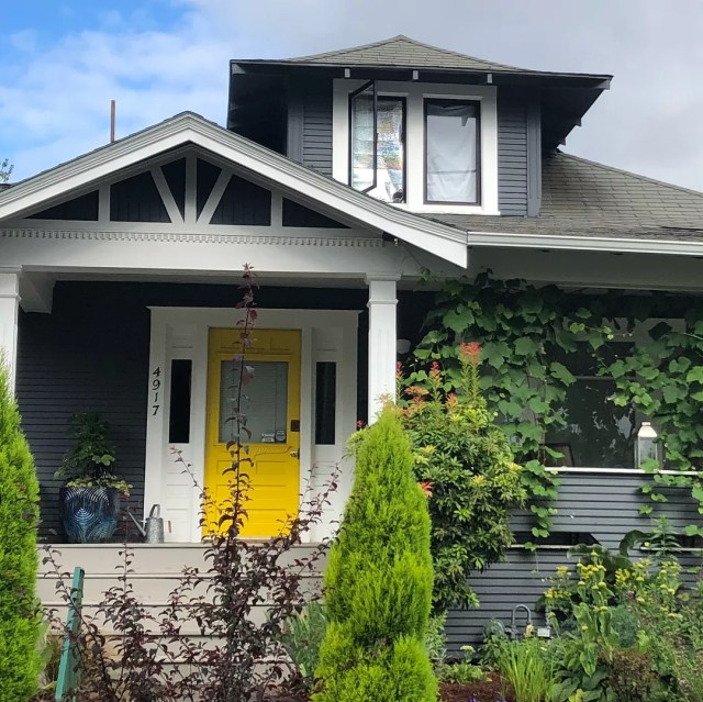 Gray house with white trim and a yellow door in King, Portland. Photo by Instagram user @lizzychun