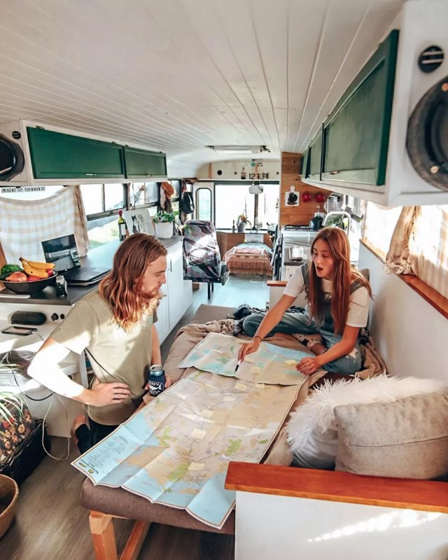 Couple planning a trip on a map in their van. Photo by Instagram user @thejahbus