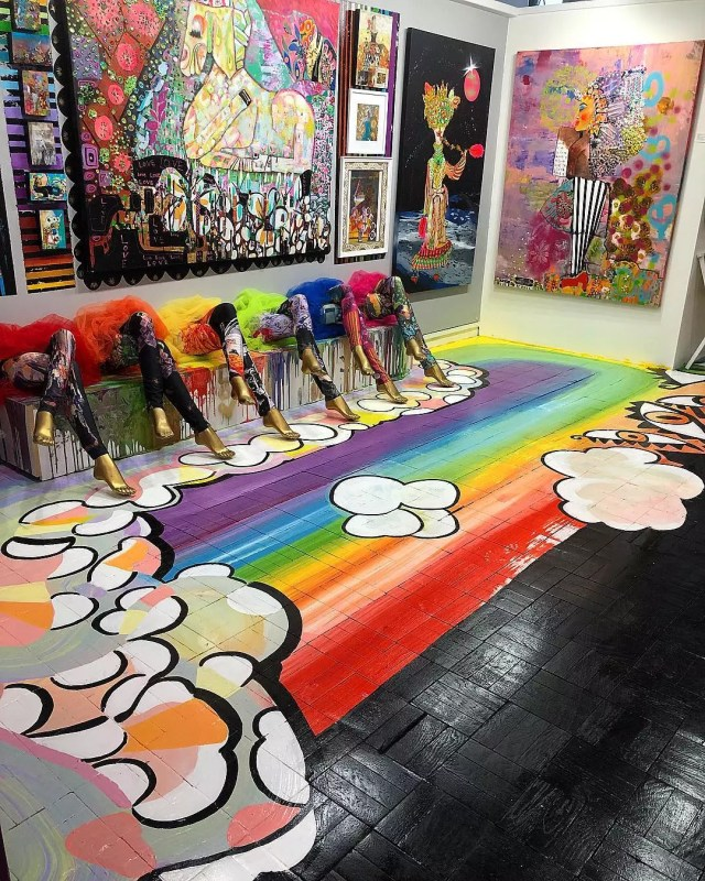 Room in an art museum with bright art on the wall and rainbows on the floor. Photo by Instagram user @omiexperience