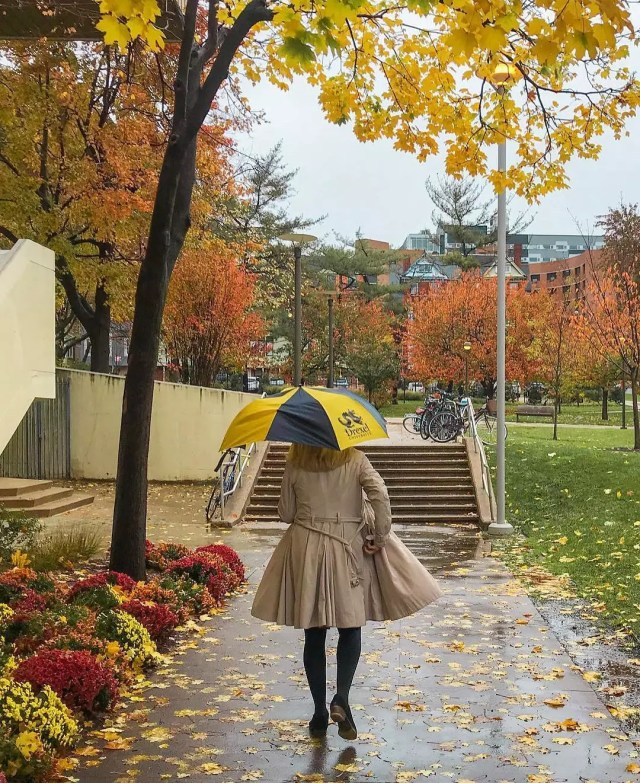 Girl walking on a college campus with an umbrella. Photo by Instagram user @pavlosmixalis