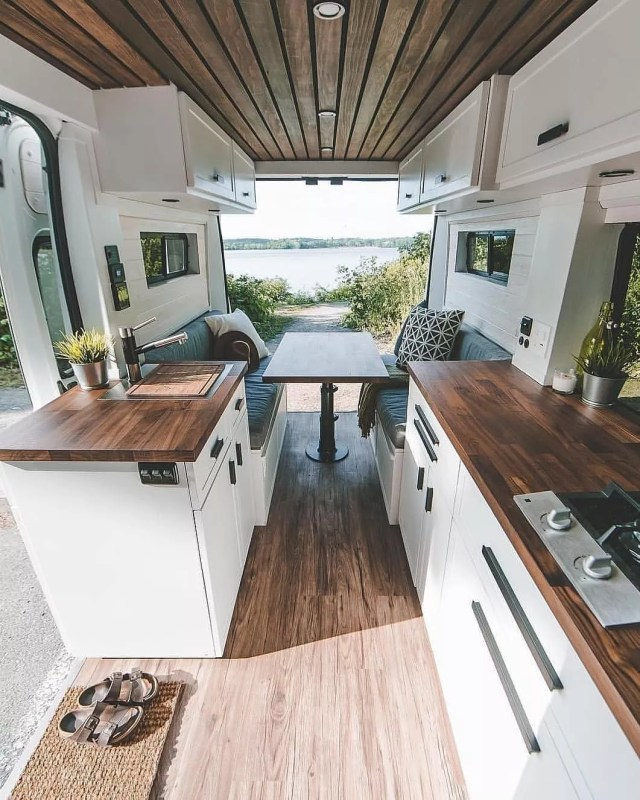 Van dining area with white cabinets and brown counters.Photo by Instagram user @vanlifevirals
