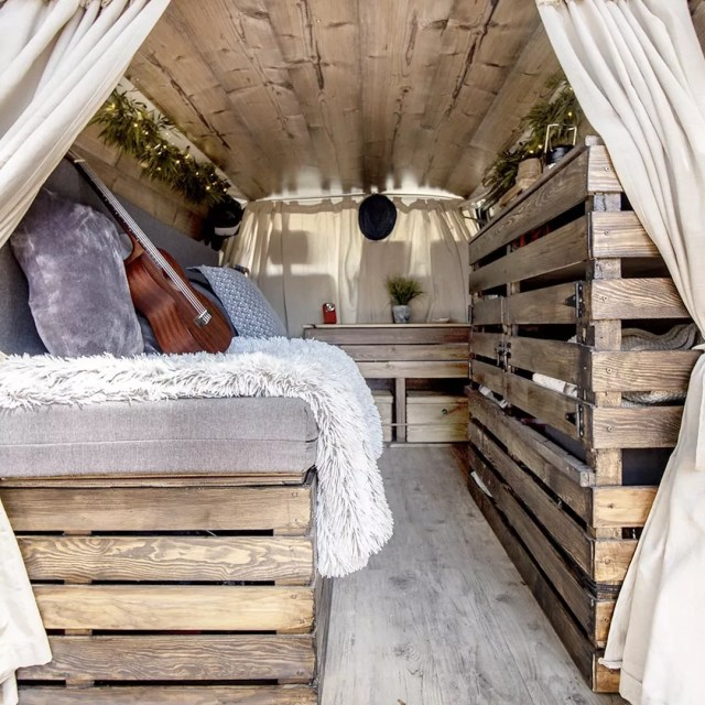 Back of van with wood bed frame and white curtains. Photo by Instagram user @dannyfreediver
