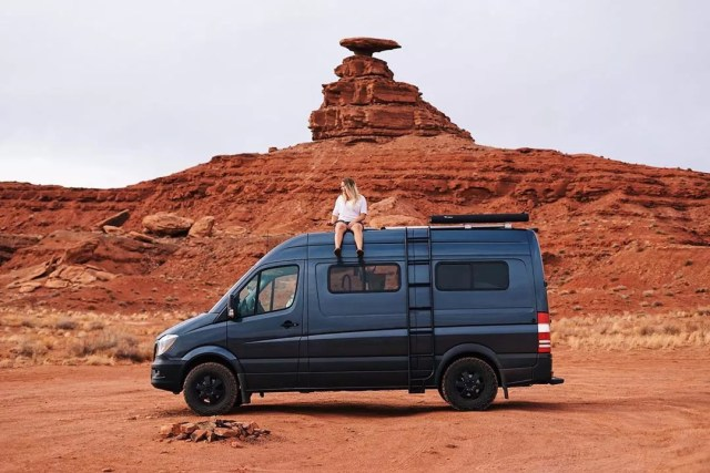 Girl sitting on the top of a van in the desert. Photo by Instagram user @soweboughtavan