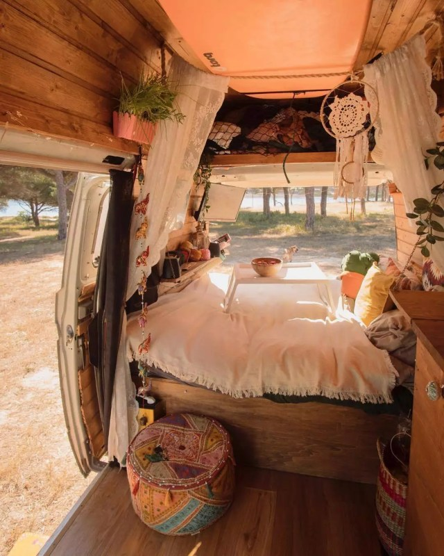 Plants hanging in a van with a white bed. Photo by Instagram user @susicruzz