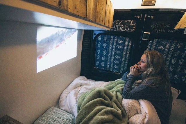 Girl watching TV with a projector and wall. Photo by Instagram user @repoweredram